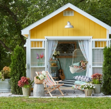 yellow-and-white-little-house-with-curtains-on-the-door-she-shed-images-a-swing-a-guitar-and-other-items-inside-e1537830609411